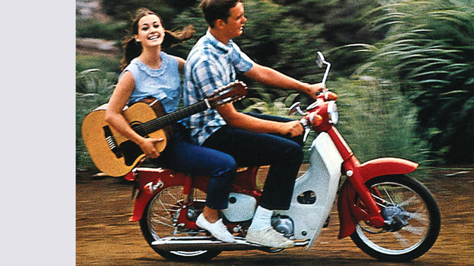 Kleine Honda mit Fahrer und Beifahrer mit Gitarre. Auf Schotter. Nach rechts weisend.