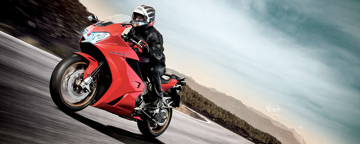 Front-facing view of VFR1200F leaning into corner with rider. Road location.